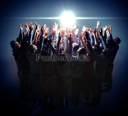 diverse group reaching for bright light