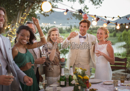 young couple and guests toasting with