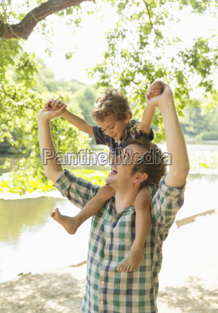 playful father carrying son on shoulders