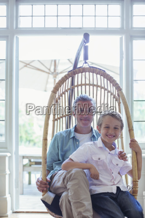 father and son sitting in wicker