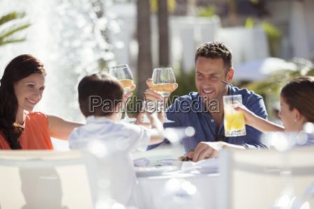 family with two children raising toast