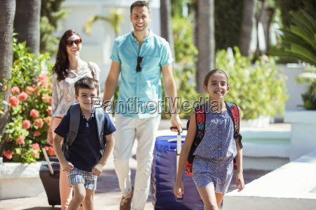 family with suitcases walking towards tourist