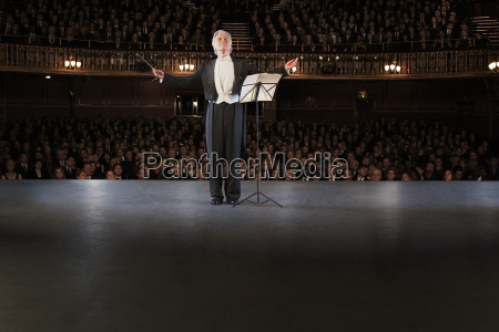 conductor performing on stage in theater