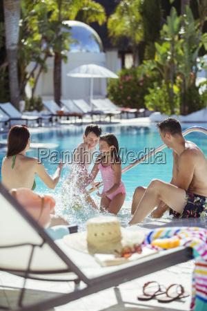family with two children splashing water