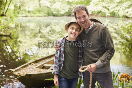 portrait father and son with boat