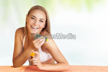 happy kobieta stosowania ochrony przeciwslonecznej