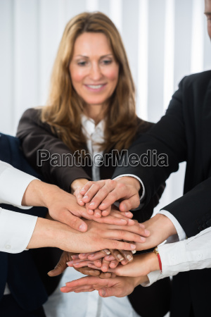 businesspeople putting hands on each other