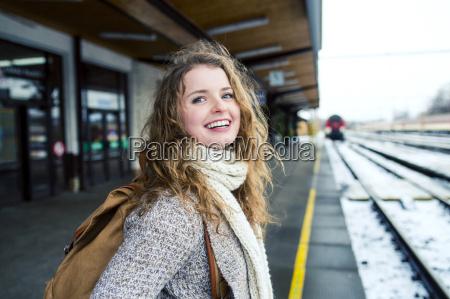 smiling teenage girl on station platform