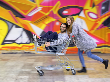 jovem mulher empurrar homem shopping carreta