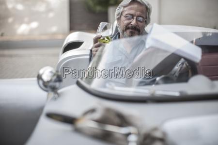 homem senior no carro de esportes