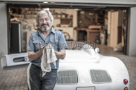 smiling senior man with cleaning cloth
