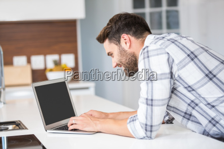 man using laptop while leaning on