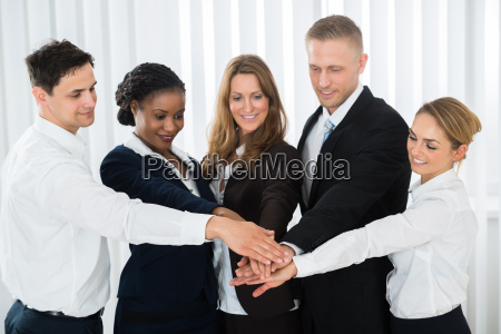 businesspeople stacking hands over each other