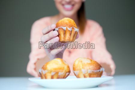 mulher nova feliz que come queques