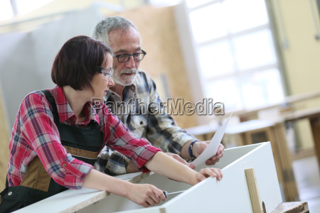 young woman with senior craftsman in