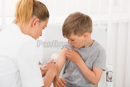 medico dando uma injecao no garoto