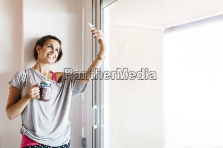 mulher jovem sorridente com bebida saudavel
