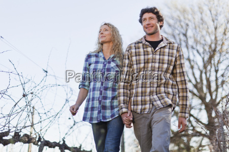 couple walking hand in hand outdoors