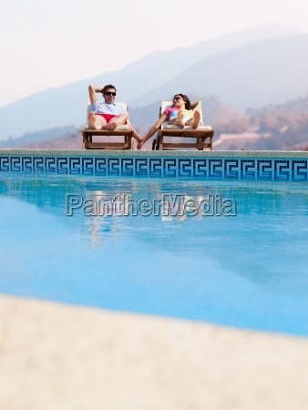 couple sunbathing by swimming pool