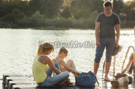 three young adult friends tying shoelaces