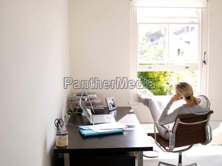 mulher sentada no escritorio em casa