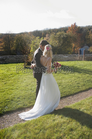 a wedding couple walking along a