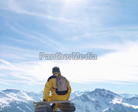 man sitting on bench on mountain