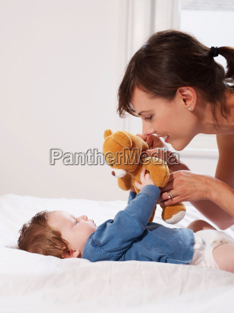 mother and baby playing with teddy