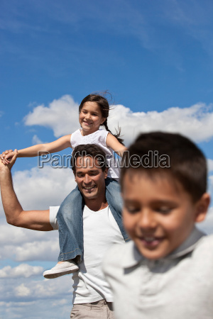father with children running in a