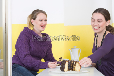 two young women eating cake