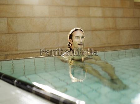 mature man sitting in swimming pool