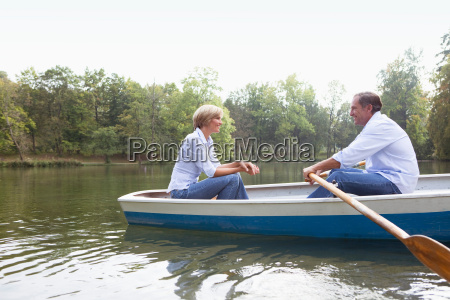 middle aged couple in a rowboat