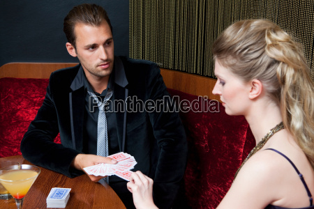 couple playing cards in bar