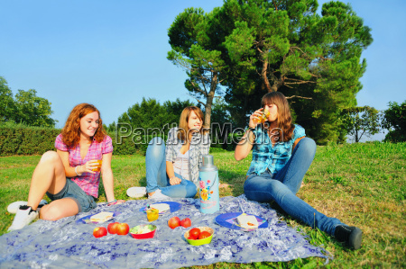teenage girls picnicking in rural field