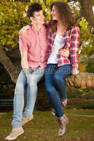 teenage couple sitting in tree in