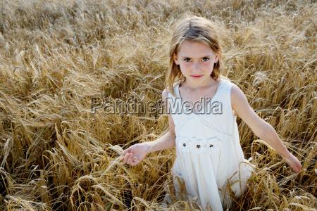 young girl walking in corn field