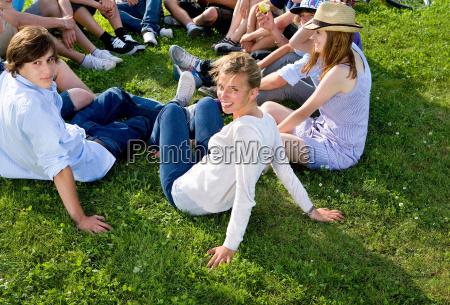 teen group sitting on grass