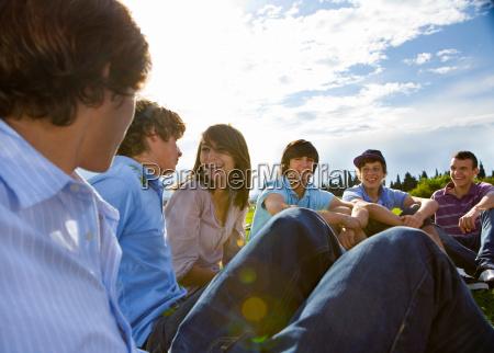 teen group sitting on grass talking