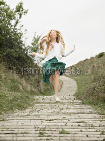 girl skipping towards camera