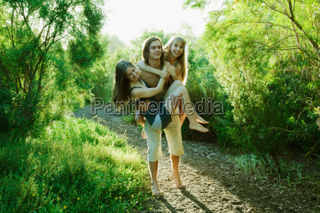 young man carrying two young women