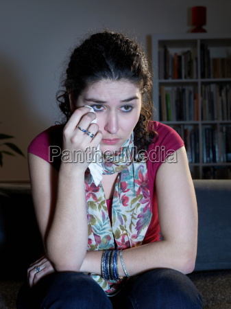 young woman weeping watching television