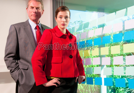 two business people with wall of