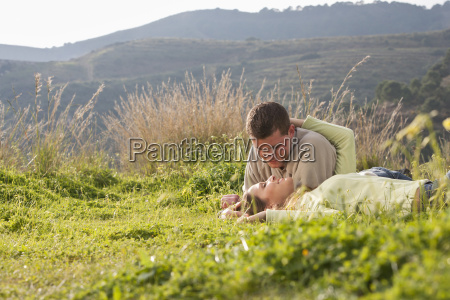 young loving couple lying in field