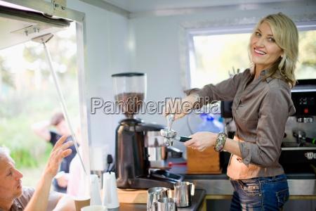 woman making coffee in food cart
