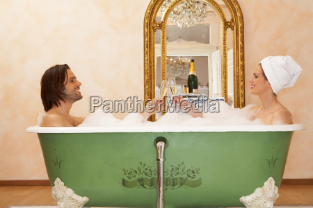 young couple sitting in bath toasting