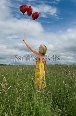 woman holding balloons in field