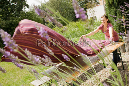 woman laying table cloth on table