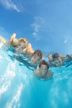 group of friends submerged in pool