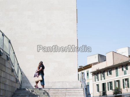 couple embracing at top of stairs
