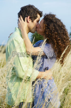 couple kissing in a wheat field